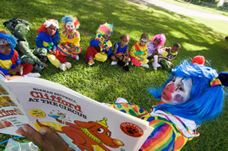 A clown reading to kids.
